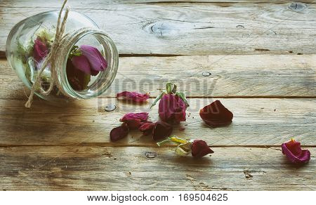 dry rosebuds in a glass jar on a wooden table vintage style