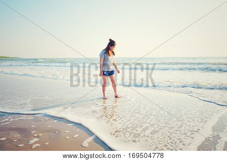 Young woman traveler relaxing on a perfect beach. Technical Writing light synthesizer. vintage and hipster tone.