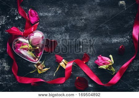 Valentine's Day composition with dried roses ribbon transparent heart box on black an old metal surface location from left