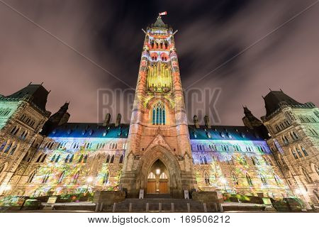 Winter holiday light show projected at night on the Canadian House of Parliament to celebrate the 150th Anniversary of Confederation of Canada in Ottawa, Canada.
