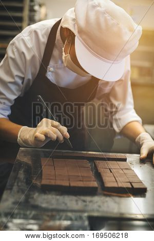 Chef cutting homemade chocolate in kitchen.  Food concept