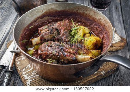 Lamb Knuckles with Fried Potatoes in Burgundy Sauce in Casserole