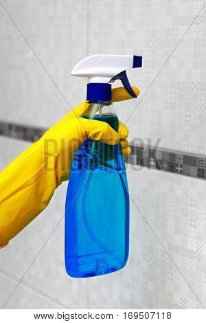 Hand in yellow glove holding spray for cleaning