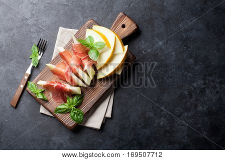 Fresh melon with prosciutto and basil. Antipasti. Top view on dark stone table with copy space