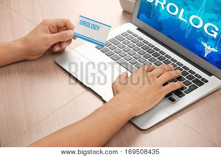 Man searching internet information on urology, close up view