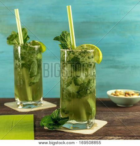A square photo of mojito cocktails with mint leaves, wedges of lime, drinking straws and a snack, on a vibrant teal wooden background with copy space. Selective focus