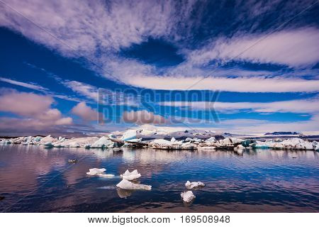 The ice floes and cirrocumulus clouds of lagoon Jokulsarlon, Iceland. The concept of northern extreme tourism. Cirrocumulus magically reflected in the smooth water of the lagoon