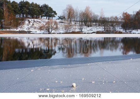 Winter landscape. Ice on lake and reflection of trees in water.