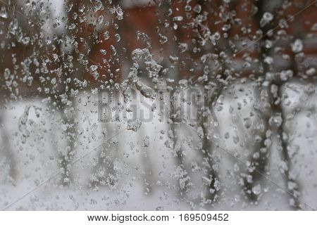 Wet snow on a windowpane - water drops and snowflakes