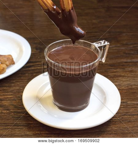 A square photo of churros, traditional Spanish, and especially Madrid, dessert, particularly for Sunday breakfast, dipped into hot chocolate. With a place for text