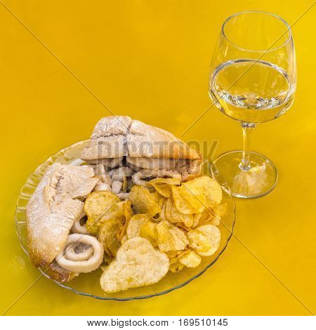 A square photo of a squid sandwich, traditional Madrid snack, with a glass of white wine, on a vibrant yellow background, with copy space