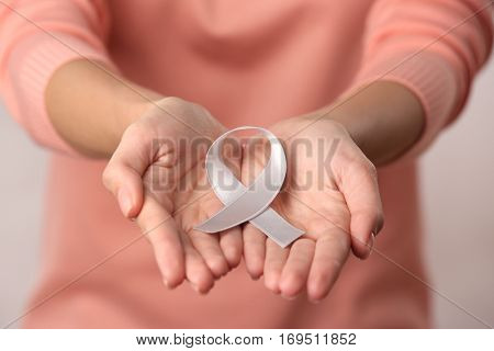 Close up view of female hands holding white ribbon. Violence against women and heterosexual family concept