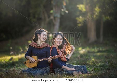 Happy asian woman in traditional she sing a song and play pin (Thai akulele)