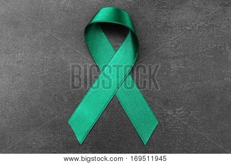 Green ribbon on dark background. Mitochondrial diseases and kidney cancer concept