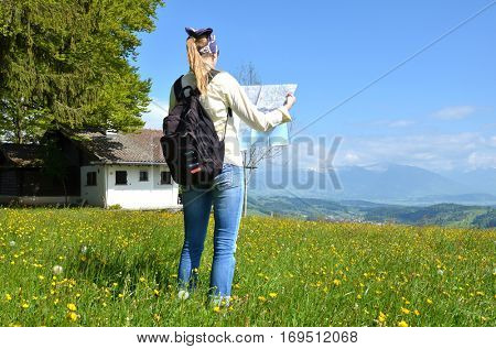 Traveler with a map against Alpine scenery