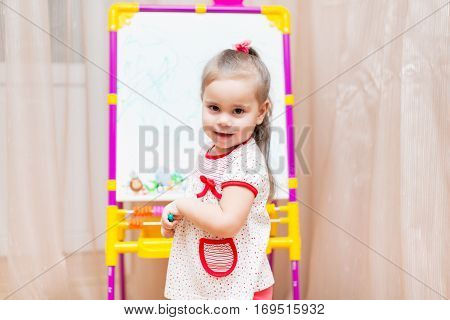 Little child girl drawing on white board