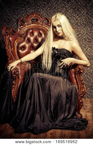 Gothic style. Beautiful young woman with long blonde hair and black make-up wearing long black dress. Vintage interior, castle style. Halloween.
