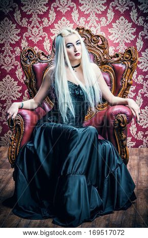 Beautiful gothic woman with long blonde hair wearing black dress. Vintage interior, castle style. Halloween.