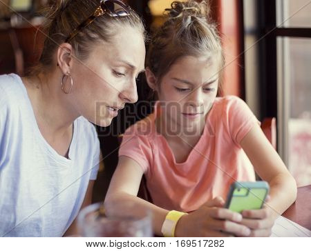 Concerned and cautious mother is looking at her daughter using her smart phone. She is watching closely at and teaching her daughter how to user her smart phone