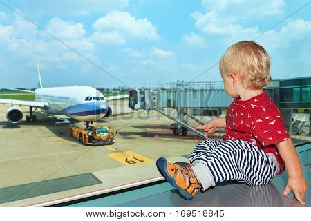 Little baby boy waiting boarding to flight in airport transit hall and looking through the window at airplane near departure gate. Active family lifestyle travel by air with child on summer vacation