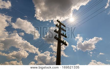 Old telegraph pole, profiled on sky with cumulus clouds, on a bright, sunny, day