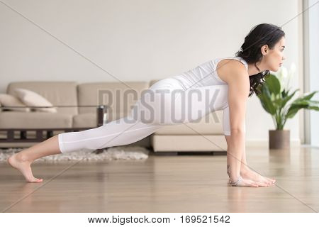 Young attractive woman practicing yoga at home, stretching in Utthan Pristhasana exercise, Lizard pose, working out, wearing white clothes, indoor full length, living room, near sofa