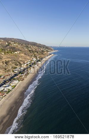Aerial of sandy beaches and upscale homes on the Southern California coast in Malibu.