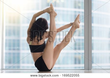 Young woman practicing yoga, doing Both big toe exercise, variation of Navasana pose working out, wearing sportswear, black tank top, shorts, full length, near floor window with city scenery, back view