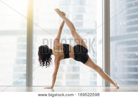 Young sporty woman practicing yoga, standing in Full Version of Vasisthasana exercise, Side Plank pose, working out wearing sportswear black tank top, shorts, full length, near floor window, rear view