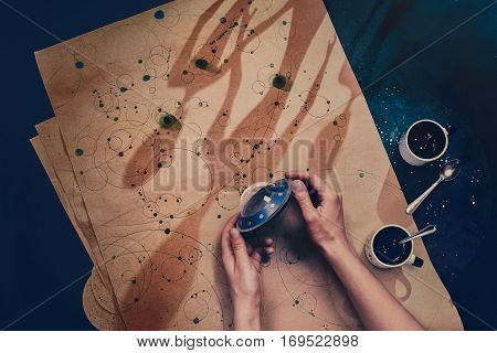 High angle shot of hands holding a small flying saucer made from paper with a star map on a craft paper and dark shadows in a shape of