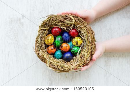Child Holding A Nest With Colored Easter Eggs At Home On Easter Day