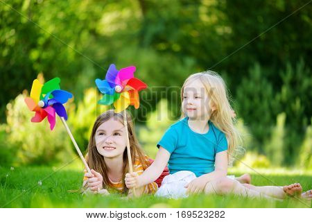 Two Cute Little Girls Holding Colorful Toy Pinwheels On Warm And Summer Day