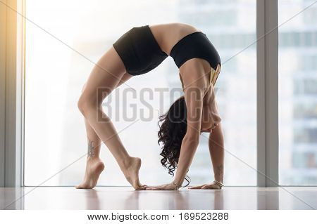 Young sporty woman practicing yoga, standing in Urdhva Dhanurasana exercise, Bridge pose, working out, wearing sportswear, black tank top, shorts, indoor full length, near floor window with city view