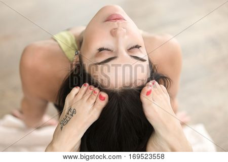 Top view of young attractive woman doing King Cobra pose, Raja bhudjangasana exercise with tattoo on her foot meaning Wild kitty , short red nails, feet with pedicure, closeup, closed eyes