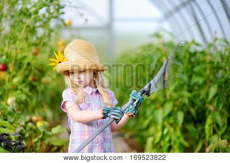 Adorable Little Girl Wearing Straw Hat And Childrens Garden Gloves Playing With Her Toy Garden Tools