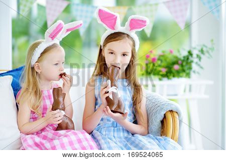 Two Cute Little Sisters Wearing Bunny Ears Eating Chocolate Easter Rabbits