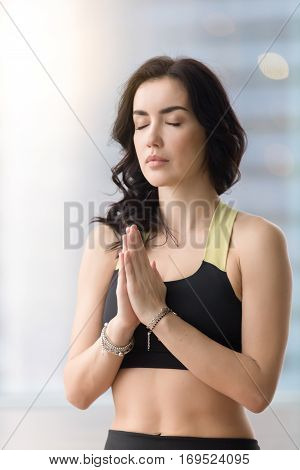 Portrait of young attractive woman practicing yoga, making namaste gesture, working out, wearing sportswear, black tank top, eyes closed, near window, wrists with bracelets. Meditation session concept