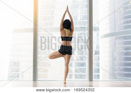 Young attractive woman practicing yoga, standing in Vrksasana exercise, Tree pose, working out, wearing sportswear, black tank top, shorts, indoor full length, near floor window with city, rear view