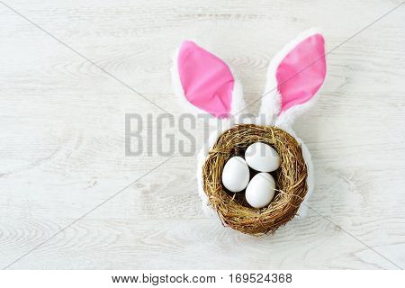 A Nest With Three White Easter Eggs And Bunny Ears At Home On Easter Day