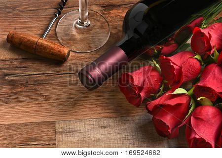 Valentines Day still life. A wine bottle with red roses and a glass and cork screw on a rustic wood table with copy space.