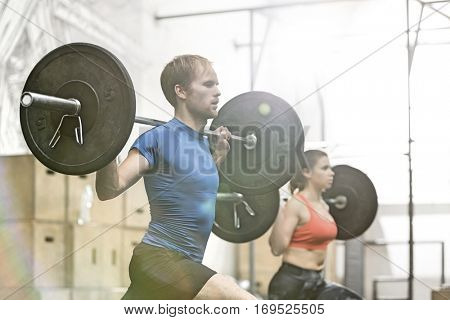 Dedicated man lifting barbell in gym