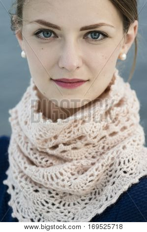 Portrait of young attractive woman wearing lacy crochet snood. Lovely discrete smile. Perfect skin.