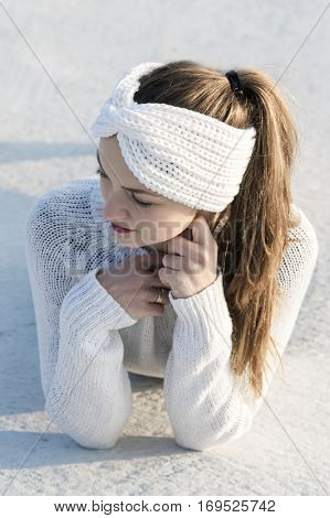 Young attractive woman wearing white knitted sweater and ear warmer turban.