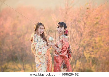 Portrait of Asian (Japanese) girls in traditional suit (Kimono) with pink cherry blossom background