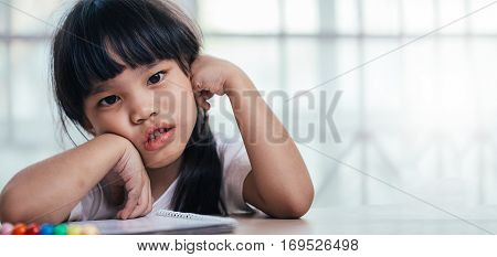 schoolgirl childhood and education concept asia girl exasperated with his homework