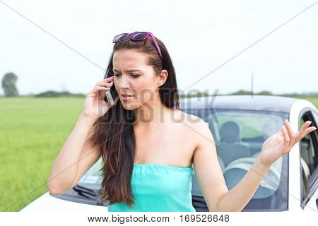 Frustrated woman using cell phone against broken down car