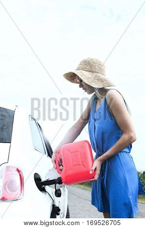 Side view of woman refueling car on country road