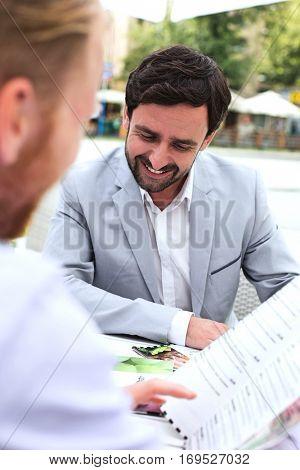 Businessmen deciding menu at sidewalk cafe