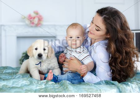 Little boy with short blond hair, barefoot, sitting on the bed on a turquoise blanket with her mother, a beautiful woman with long curly hair, black hair, wearing a white shirt and blue jeans, along with them - a pet, puppy golden retriever, happy family
