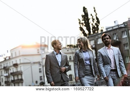 Businesspeople walking in city on sunny day